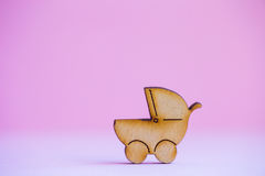 Wooden icon of baby buggy on pink background Royalty Free Stock Images