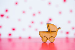 Wooden icon of baby buggy on pink and white background Royalty Free Stock Image