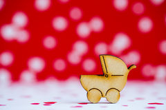 Wooden icon of baby buggy on red and white background Stock Photos