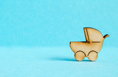 Wooden icon of baby carriage on blue background Stock Photos