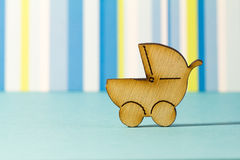 Wooden icon of baby carriage on blue striped background Stock Images