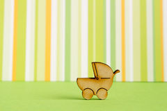 Wooden icon of baby carriage on green striped background.  Stock Photos