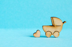 Wooden icon of baby carriage and little heart on blue background Stock Image