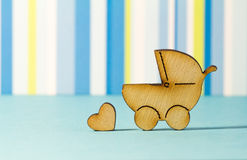 Wooden icon of baby carriage and little heart on blue striped ba Stock Images