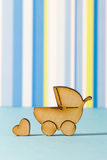 Wooden icon of baby carriage and little heart on blue striped ba Stock Photo