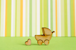 Wooden icon of baby carriage and little heart on green striped b Stock Photo