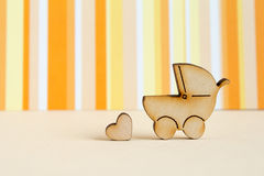 Wooden icon of baby carriage and little heart on orange striped. Background horizontal Stock Photo