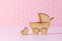Wooden icon of baby carriage and little heart on pink background Stock Photography