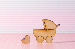 Wooden icon of baby carriage and little heart on pink striped ba Royalty Free Stock Photography