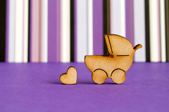 Wooden icon of baby carriage and little heart on purple striped Stock Photos
