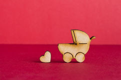 Wooden icon of baby carriage and little heart on red background Royalty Free Stock Images