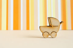 Wooden icon of baby carriage on orange striped background.  Royalty Free Stock Photos