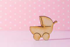 Wooden icon of baby carriage on pink background Stock Image