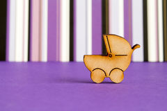 Wooden icon of baby carriage on purple striped background.  Royalty Free Stock Photos
