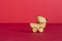 Wooden icon of baby carriage on red background.  Royalty Free Stock Photography