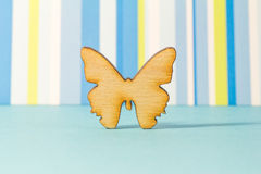 Wooden icon of butterfly on blue striped background Royalty Free Stock Photography
