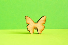Wooden icon of butterfly on green background. Horizontal Stock Photos
