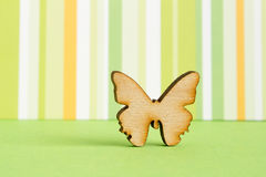 Wooden icon of butterfly on green striped background. Horizontal Royalty Free Stock Photos