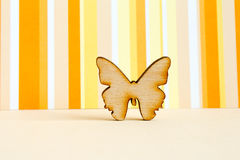Wooden icon of butterfly on orange striped background. Horizontal Royalty Free Stock Images