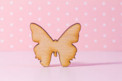 Wooden icon of butterfly on pink background Royalty Free Stock Images
