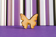 Wooden icon of butterfly on purple striped background. Horizontal Stock Photo