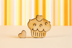Wooden icon of cake with little heart on orange striped backgrou Stock Images