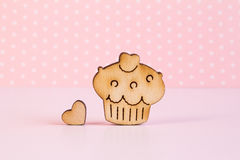 Wooden icon of cake with little heart on pink background Stock Photo