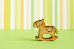 Wooden icon of children's rocking horse on green striped  backg. Round horizontal Royalty Free Stock Images