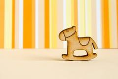 Wooden icon of children's rocking horse on orange striped backgr. Ound horizontal Stock Image