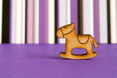 Wooden icon of children's rocking horse on purple striped backgr. Ound horizontal Stock Image