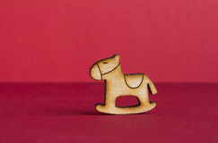 Wooden icon of children's rocking horse on red background. Horizontal Stock Photography