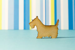 Wooden icon of dog on blue striped background Stock Image