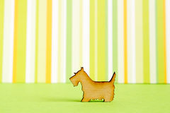 Wooden icon of dog on green striped background. Horizontal Stock Photography
