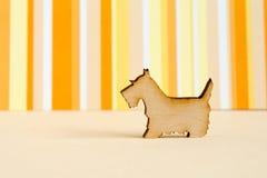 Wooden icon of dog on orange striped background. Horizontal Stock Photo