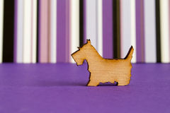 Wooden icon of dog on purple striped background. Horizontal Stock Photography