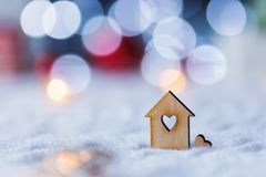 Wooden icon of house with hole in form of heart with red home Christmas decor and blurred bokeh background in daylight