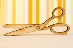 Wooden icon of scissors on orange striped background Royalty Free Stock Photos