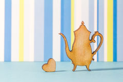 Wooden icon of teapot with little heart on blue striped backgrou Stock Image