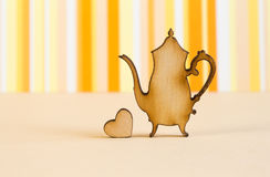Wooden icon of teapot with little heart on orange striped backgr Stock Images