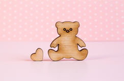 Wooden icon of Teddy bear with little heart on pink background Stock Photos