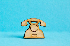 Wooden icon of telephone on blue background Royalty Free Stock Photo