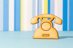 Wooden icon of telephone on blue striped background Stock Image