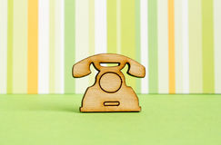 Wooden icon of telephone on green striped background. Horizontal Royalty Free Stock Photo