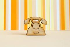 Wooden icon of telephone on orange striped background. Horizontal Royalty Free Stock Images