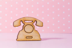 Wooden icon of telephone on pink background Royalty Free Stock Image