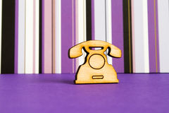 Wooden icon of telephone on purple striped background Stock Images