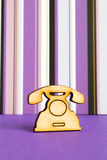 Wooden icon of telephone on purple striped background. Vertical Royalty Free Stock Images