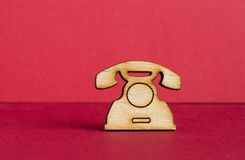 Wooden icon of telephone on red background Stock Photos