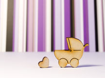 Wooden icons of baby carriage and heart on a white surface and p. Urple striped background Stock Photography