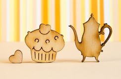 Wooden icons of cake and teapot with little heart on orange stri Stock Photo